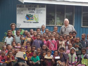 Specialty Green Coffee Importer, Andrew Vournas with Papua New Guinea school children receiving supplies and support from Vournas Coffee Trading