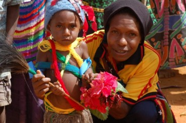 PNG Coffee Farmer and Her Child Holding Flowers