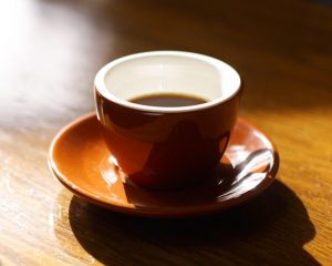 Morning sunlight shining on a closeup of a coffee cup with saucer and black coffee.