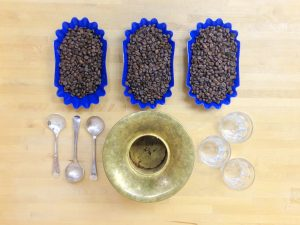 Specialty Coffee Cupping Setup with Roasted Coffee, Silver Spoons, and Spitoon