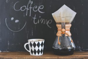 "Classic Chemex coffee brewer next to ""coffee time"" blackboard"