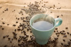 Mug of hot coffee pictured with roasted coffee beans on burlap