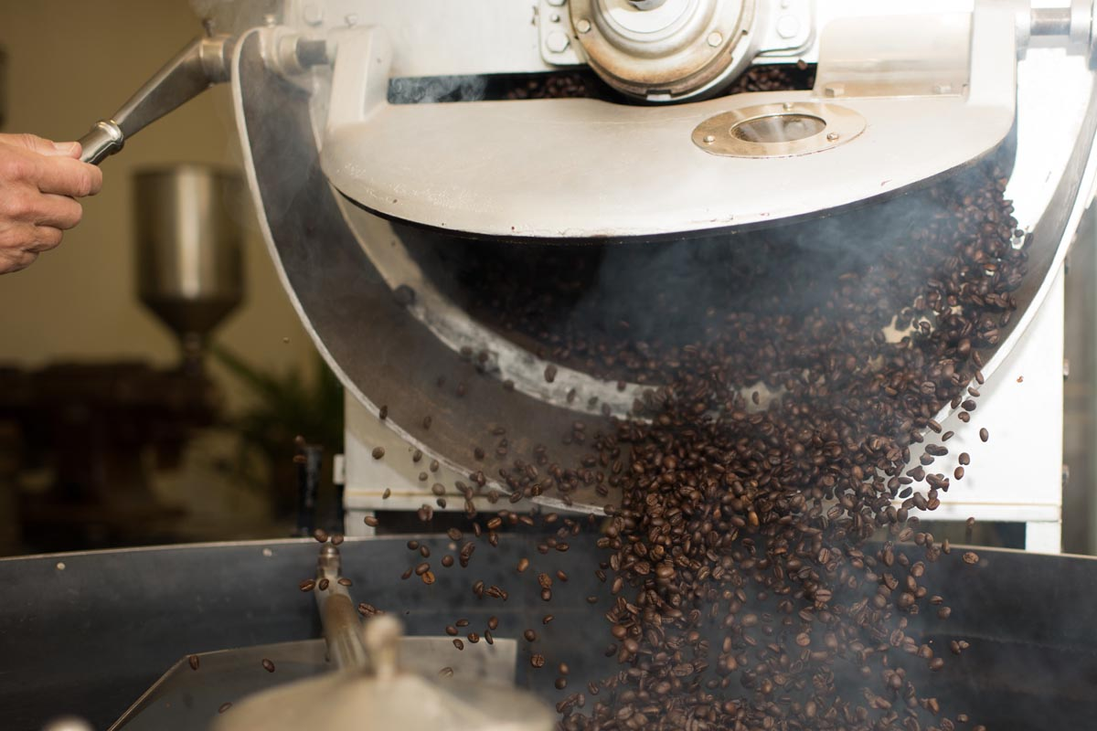Coffee roaster and machine dropping roasted coffee into cooling tray